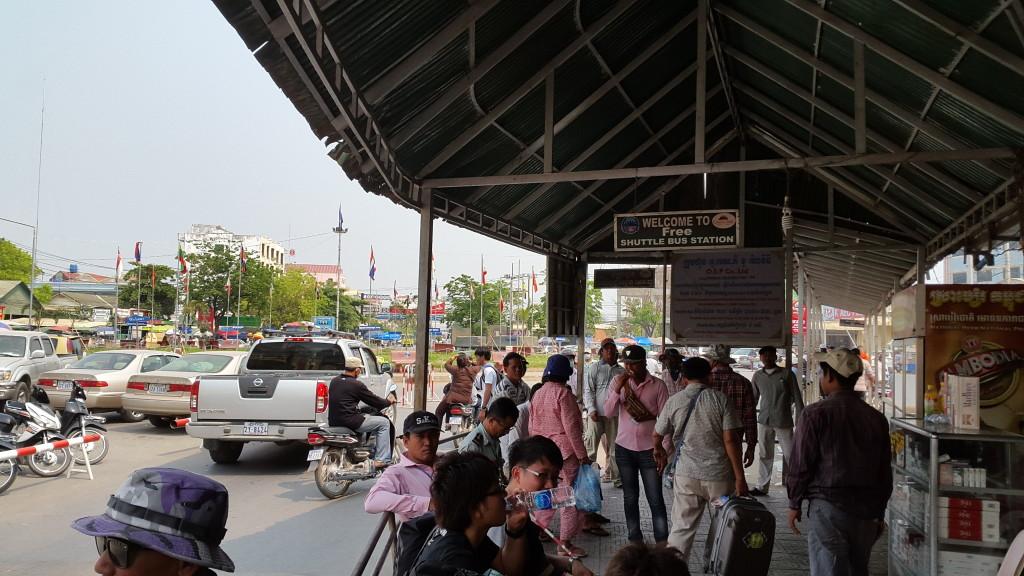 Фото с этой же точки, но в сторону Камбоджи. Сверху висит табличка про бесплатный автобус. Также обратите внимание на местный в розовых рубашкам - это те самые приставалы-помогалы.